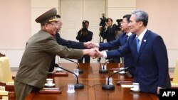 Представники Південної Кореї тиснуть руки північнокорейським колегам. Село Пханмунджон, демілітаризована зона, 22 серпня 2015 р.