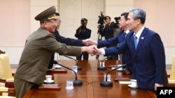 This handout photo from the S. Korean Unification Ministry shows the S. Korean president's national security adviser, Kim Kwan-Jin (R), and Unification Minister Hong Yong-Pyo (2nd R) shaking hands with the N. Korean officials during their meeting, Aug. 22, 2015.