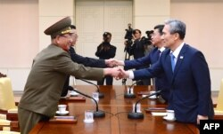 South Korean National Security Director Kim Kwan-jin, right, and Unification Minister Hong Yong-pyo, second from right, shake hands with Hwang Pyong So, left, top political officer for North Korea'ss Army, and Kim Yang Gon, a senior North Korean official responsible for South Korean affairs, during a meeting in Paju, South Korea, Aug. 22, 2015.