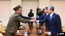 Penasihat keamanan nasional kepresidenan Korea Selatan Kim Kwan-Jin (kanan), dan Menteri Unifikasi Hong Yong-Pyo (kedua dari kanan) berjabatan tangan dengan pejabat tinggi militer Korea Utara Hwang Pyong-So (kiri) dan pejabat tinggi urusan Korea Selatan Kim Yang-Gon (kedua dari kiri) dalam pertemuan di desa Panmunjom (22/8).