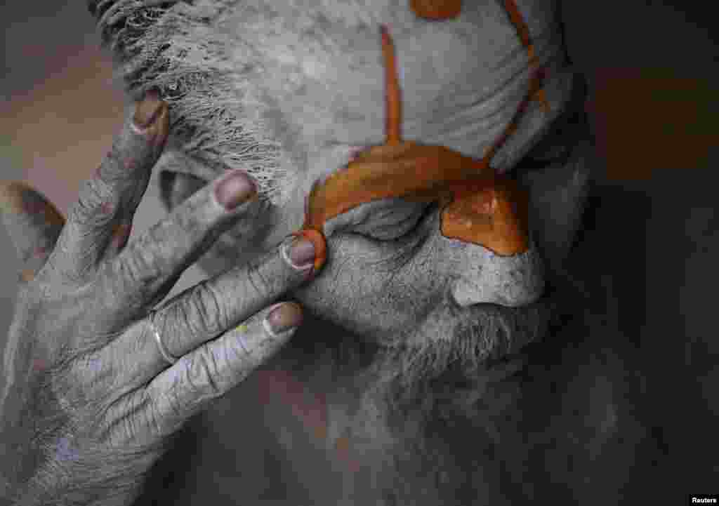 A Hindu sadhu (holy man) applies paint to his forehead at his ashram on the premises of Pashupatinath Temple in Kathmandu, Nepal. Hindu holy men from Nepal and India come to the temple to take part in the Shivaratri festival, which this year falls on March 10.