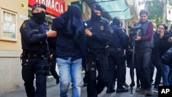 Des policiers de Mossos d'Esquadra, la police de la région de Catalogne, emmènent un homme non identifié, à Barcelone, Espagne, 25 avril 2017.