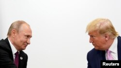 На фото: президент США Дональд Трамп та президент Росії Володимир Путін спілкуються під час саміту G20 у Японії у червні 2019-го року