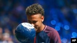 La star brésilienne Neymar fixe le regard à la balle lors de sa présentation officielle aux fans, au stade Parc des Princes à Paris, 5 août 2017.