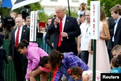 U.S. President Donald Trump blows a whistle to start the White House Easter Egg Roll alongside first lady Melania Trump and his son Barron, right, on the South Lawn of the White House in Washington, April 17, 2017.
