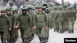 Uniformed men, believed to be Russian servicemen, march outside a Ukrainian military base in the village of Perevalnoye, outside Simferopol, March 5, 2014.