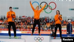 Second-placed Sven Kramer (L) of the Netherlands and his compatriot third-placed Bob de Jong (R) applaud winner Jorrit Bergsma of the Netherlands, during the flower ceremony for the men's 10,000 meters speed skating race at the Adler Arena, in the Sochi 2