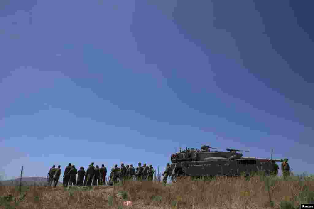 Israeli soldiers stand next to a tank near Alonei Habashan on the Israeli occupied Golan Heights, close to the ceasefire line between Israel and Syria, June 22, 2014.
