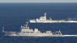An aerial photo from a Kyodo News aircraft shows the Chinese marine surveillance ship Haijian No. 51 (front) cruising as a Japan Coast Guard ship sails near the disputed islands, called Senkaku in Japan and Diaoyu in China, in the East China Sea, Septembe