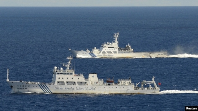 Aerial photo from Kyodo News aircraft show Chinese marine surveillance ship Haijian No. 51, front, as Japan Coast Guard ship sails near disputed islands, East China Sea, Sept. 15, 2012.