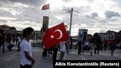 Un homme tient le drapeau turc sur la place Taksim à Istanbul, Turquie, le 20 juillet 2016.
