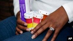 Trong ảnh tư liệu ngày 24/2/2015 này, bệnh nhân tên Kimberly Davis ở Jackson, Mississippi, cầm các lọ thuốc mà bà đang dùng để kéo chậm lại chứng đa xơ cứng.