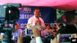 Opposition Cambodia National Rescue Party leader Sam Rainsy speaks at his party headquarters of Chak Angre Leu to celebrate his party's one year anniversary, in Phnom Penh, Cambodia, Monday, April 7, 2014. (AP Photo/Heng Sinith)