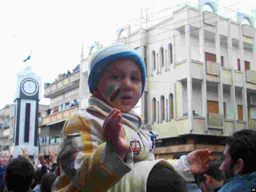 A child is pictured as demonstrators protest Syria's President Bashar al-Assad in Khalidieh, near Homs, January 15, 2012. (Reuters)
