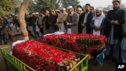 Dolientes entierran a dos víctimas del ataque a la escuela en Peshawar, Pakistán.