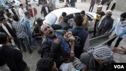 Para demonstran menolong rekan mereka yang terluka dalam bentrokan dengan pasukan keamanan Yaman di Sana'a (24/12). Sedikitnya 9 orang tewas dalam bentrokan ini.