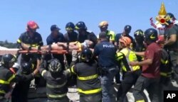 Eleven-year-old Ciro is carried on a stretcher after being rescued by Italian firefighters from the rubble of a collapsed building in Casamicciola, on the island of Ischia, near Naples, Italy, Aug. 22, 2017, a day after a 4.0-magnitude quake hit the Italian resort town.