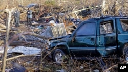 A vehicle sits among debris near Linden, Tenn., Dec. 24, 2015, following rare Christmastime tornadoes.