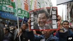 Warga berunjuk rasa dengan memegang foto pemimpin kota Hong Kong Leung Chun-ying di awal Tahun Baru 1 Januari 2013. (AP Photo/Kin Cheung)