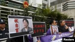 香港抗議者在北京駐香港機構中聯辦前手舉銅鑼灣書店失踪老闆桂民海的照片。(2016年1月19日)