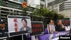 香港抗議者在北京駐香港機構中聯辦前手舉銅鑼灣書店失踪老闆桂民海的照片。 (資料圖片)