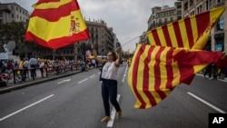 2017年10月12日,一名婦女在西班牙國慶日在巴塞羅那街頭揮舞加泰羅尼亞的西班牙的旗幟。