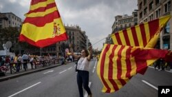 "A woman waves flags of Catalonia and Spain as people celebrate a holiday known as ""Dia de la Hispanidad"" or Spain's National Day in Barcelona, Spain, Oct. 12, 2017."
