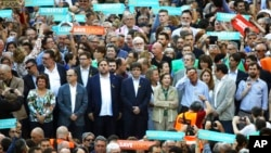 Catalan President Carles Puigdemont, second row ,center, takes part at a march to protest against the National Court's decision to imprison civil society leaders, in Barcelona, Spain, Saturday, Oct. 21, 2017. (AP Photo/Emilio Morenatti)