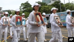 In this 2012 file photo, members of Falun Gong in Taiwan hold portraits of victims during a protest against Chinese government's policy against its members in China.