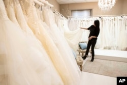 FILE - Anita Galafate checks wedding dresses in a shop in Rome, Tuesday, March 9, 2021. Couples in the U.S. are racing to the altar amid a vaccination-era wedding boom that has venues and other vendors in high demand. (AP Photo/Alessandra Tarantino, File