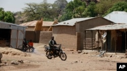 FILE - An unidentified man rides a motorbike past houses in Chibok, Nigeria, May 19, 2014. Boko Haram fighters have returned to the area according to local leaders.