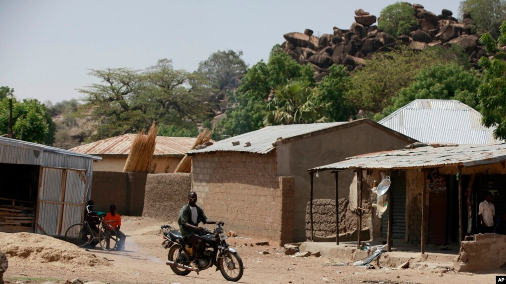 FILE - An unidentified man rides a motorbike past houses in Chibok, Nigeria, May 19, 2014.
