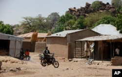 FILE - An unidentified man rides a motorbike past houses in Chibok, Nigeria, May 19, 2014. Boko Haram fighters have returned to the area, according to local leaders.