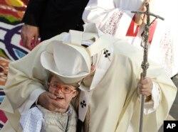 ພະສັນຕະປາປາ Francis ກອດຢອກເດັກນ້ອຍ ໃນຂະນະສະຫລອງ ພິທີສູດມົນ.