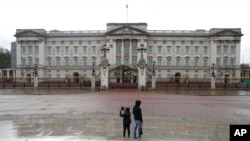 FILE - Two tourists stand in front of Buckingham Palace, one of the official homes of Britain's Queen Elizabeth II, in London, March 25, 2021. Britain is ending restrictive quarantine requirements for visitors from 47 countries, starting Oct. 11, 2021.