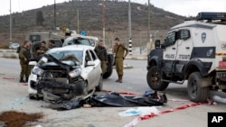 Israeli soldiers and border police officers stand near the body of a Palestinian, center, who rammed his vehicle into a group of Israelis standing at a hitchhiking station, in the West Bank, near the Palestinian town of Nablus, Nov. 8, 2015.