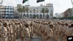 FILE - Military units under the Tripoli government stand in formation during a celebration of the 75th anniversary of the establishment of the Libyan Army in Martyrs Square, Tripoli, Aug. 13, 2015.