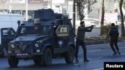 پولیس به بهرگی ئاسایی دهسترێژ له ناشتنی کوردێک له شاری دیاربهکر دهکهن که له ئهم نائارامیانهی دوایی دا کوژرا. 24ی دێسامبری 2015