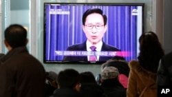 韓國人民2013年2月19日在韓國首爾的火車站觀看電視實況轉播總統李明博在發表離職前全國講話。