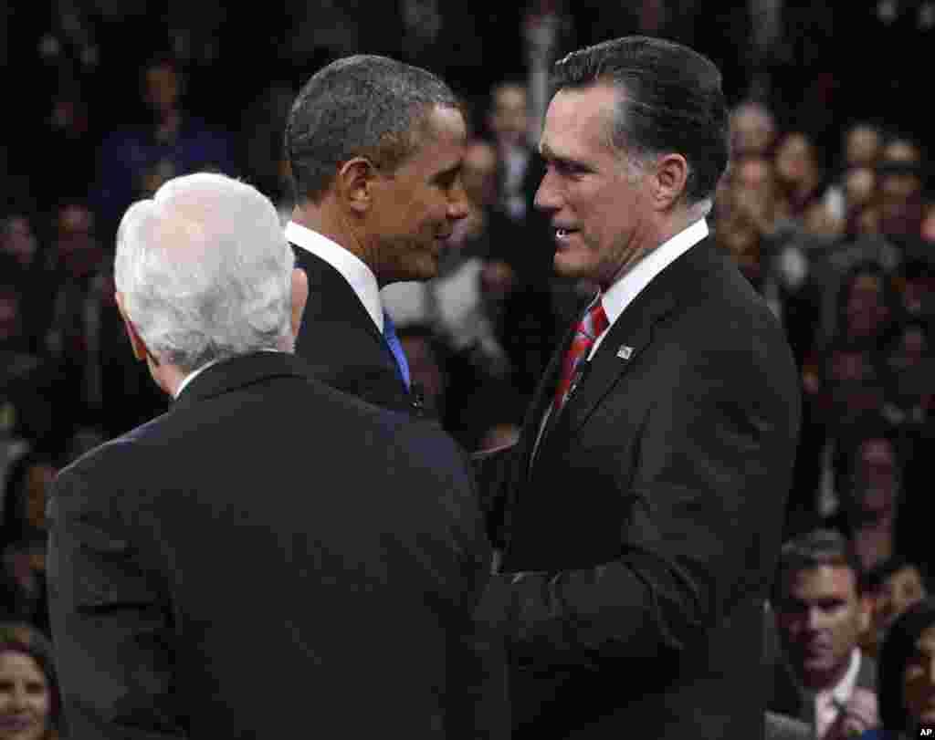Le président Obama et son adversaire républicain Mitt Romney se saluant sous le regard du journaliste Bob Schieffer
