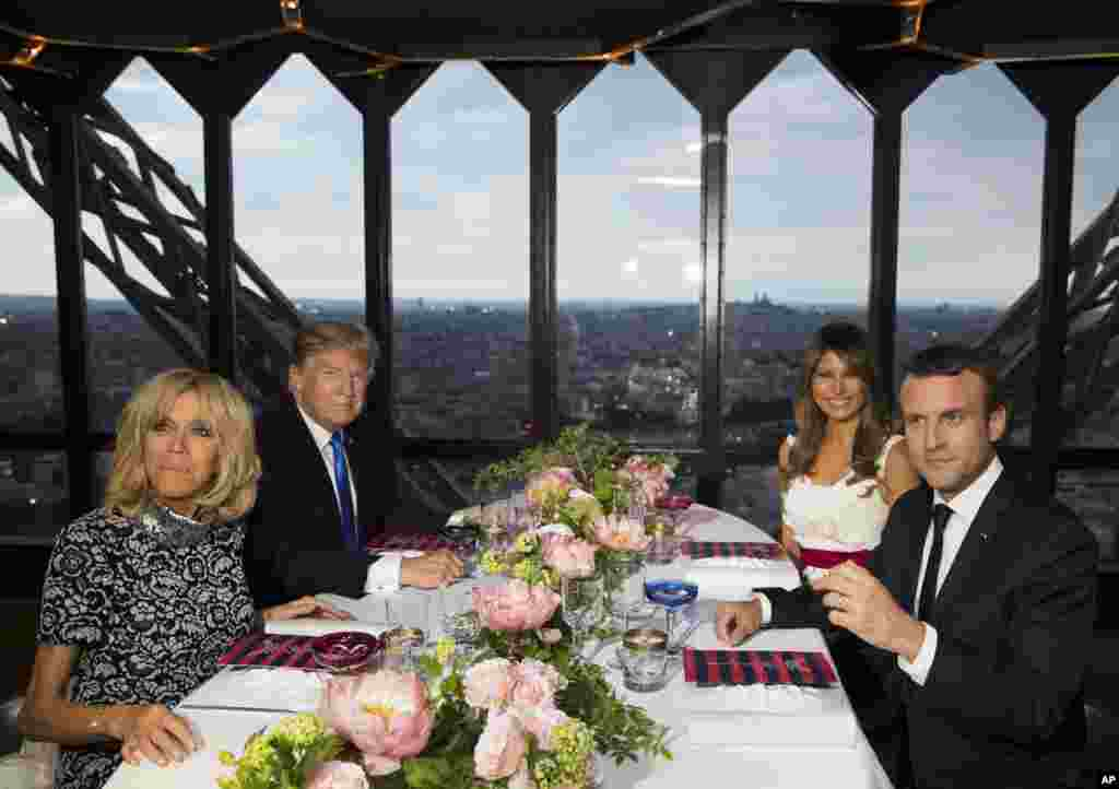 President Donald Trump, first lady Melania Trump, French President Emmanuel Macron, his wife Brigitte Macron, sit for dinner at the Jules Verne Restaurant on the Eiffel Tower in Paris.