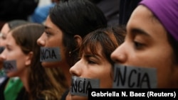 "A group of women hold a silent protest with ""Resign"" covering their mouths with tape during the seventh day of protest calling for the resignation of Governor Ricardo Rossello in San Juan, Puerto Rico July 19, 2019."
