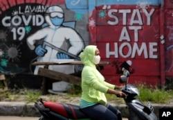 Seorang perempuan mengenakan masker mengendarai sepeda motornya melewati mural bertema Covid-19 selama pandemi corona di pinggiran Jakarta, 2 Juni 2020.