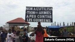 """Un manifestant brandit une pancarte indiquant """"Non à l'utilisation des armes à feu contre les Guinéens,"""" Conakry, 4 octobre 2017. (VOA/Zakaria Camara)"""