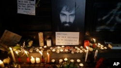 "A photo of missing activist Santiago Maldonado is surrounded by candles and a message that reads in Spanish: ""Santiago, your solidarity has made you the son of all,"" at a makeshift memorial outside the morgue, in Buenos Aires, Argentina, Oct. 20, 2017."