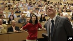 Fabiola Gianotti, Atlas team spokeswoman, and Joe Incandela, from the CMS team, look at a screen Wednesday during a scientific seminar to deliver the latest update in the search for the Higgs boson