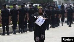 Polisi Mesir melakukan penjagaan di Sinai sementara seorang wanita melakukan unjuk rasa (foto; dok). Seorang tahanan AS di Sinai ditemukan tewas di selnya.