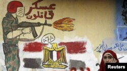 A woman sits in front of a wall filled with graffiti against the Supreme Council of the Armed Forces near Tahrir Square in Cairo, June 5, 2012.