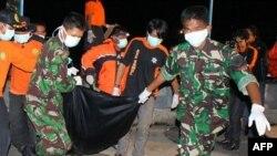 Nhân viên cứu hộ Indonesia khiêng xác một nạn nhân trong vụ sập cầu Kutai Kartanegara ở Tenggarong, ngày 29/11/2011