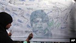 Seorang perempuan menandatangani spanduk bergambarkan Mohammad Ajmal Kasab, untuk menuntut penjatuhan hukuman mati atas pria Pakistan itu. Kasab dihukum gantung Rabu pagi pukul 7.30 (foto: Dok).